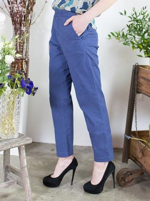 Woman wearing blue trousers made by Ash and Rose