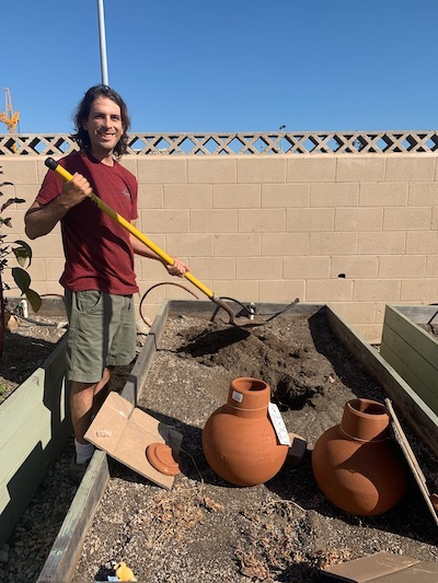 man with ollas, terracotta pots to water the garden in drought