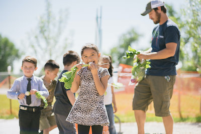 young girl eating radish with other students and teacher behind her in the climate victory garden