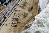 people spelling resist on the beach