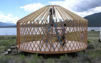 man standing inside yurt construction.