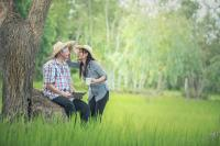 man and woman with hats standing in grass.