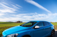 Blue Volvo vehicle driving with green field and blue sky backdrop
