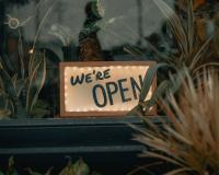 "sign in a window that reads ""we're open"" for business"