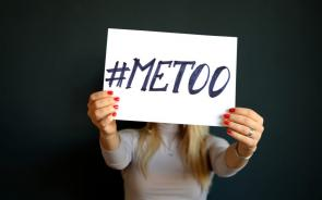 "Person with red polished fingernails holding up a ""#MeToo"" sign"