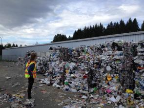 Person standing in front of a pile of recyclables