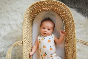 baby laying in crib wearing a onesie with oranges on it, looking curiously at the camera. The crib is wicker and is on top of a white faux fur rug.