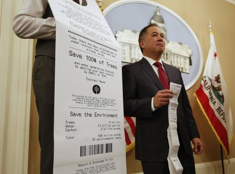 Assemblyman Phil Ting, D-San Francisco, displays a long paper receipt as he discusses his bill to require businesses to offer electronic receipts, Tuesday, Jan. 8, 2019, in Sacramento, Calif. Under the legislation customers could receive a paper receipt on request. (AP Photo/Rich Pedroncelli)