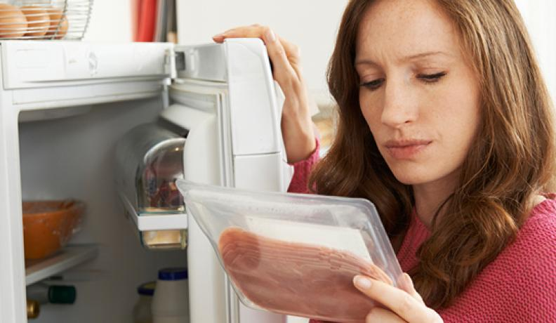woman looks at meat in her fridge