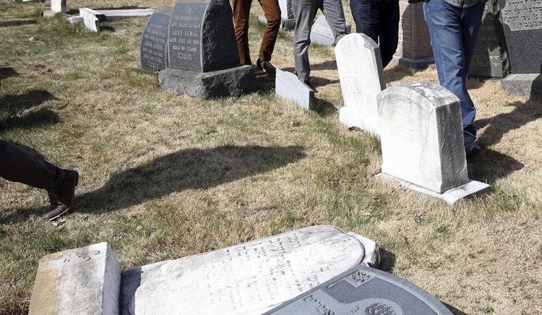 Ahmadiyya Muslim volunteers walk through Mount Carmel Cemetery in Philadelphia, where vandals desecrated Jewish headstones in February