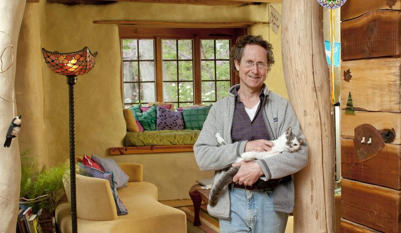 Bill Hutchins with his cat in his sunroom
