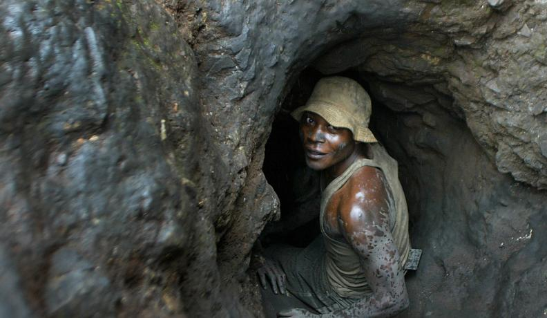 Man enters hand-dug tunnel.