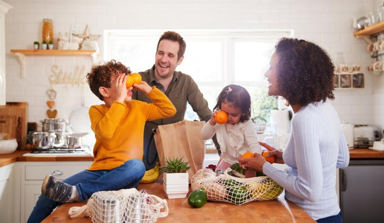 family laughing around a counter with groceries on it