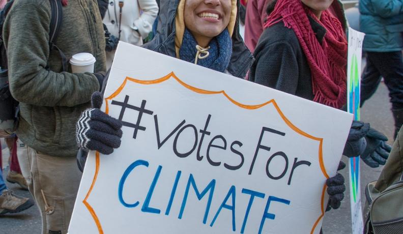 "activist with sign that reads ""hashtag Votes for Climate"""