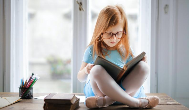 Little girl reading a book.