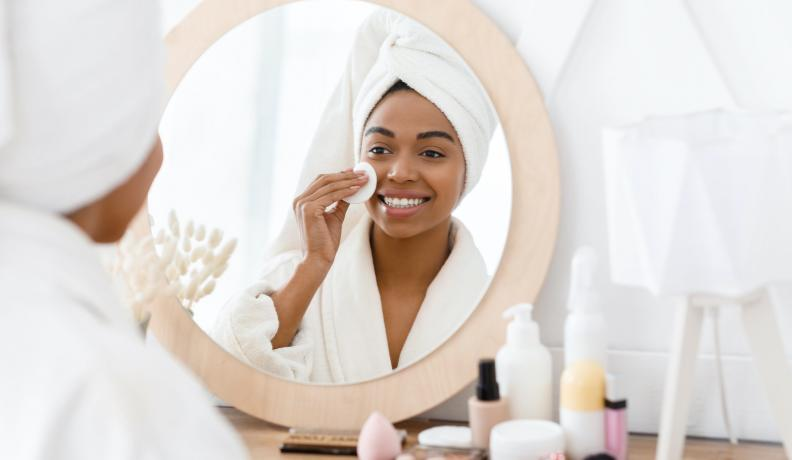 Black woman applying face products.