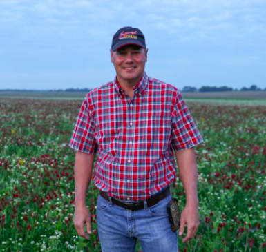 Rick Clark in field of crimson and balansa clover cover crops.