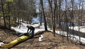 man pulls kayak out of Menominee offshoot