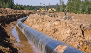 workers construct gas pipeline over groundwater