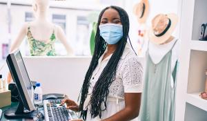 Black woman wearing mask behind cash register