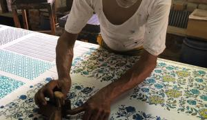 Indian man bends over a piece of cloth and applies a floral wood block print