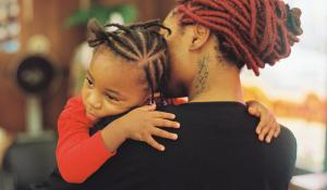 A Black mother and daughter embrace. Photo via Stocksy.
