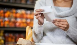 shopper in a grocery store holding a receipt